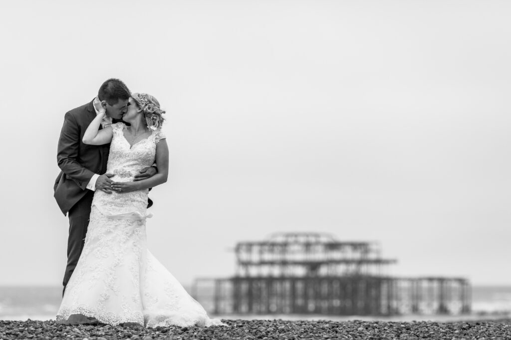 Newly weds. Happy couple kissing on Brighton beach.