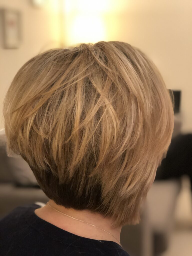 Short layered textured bob. Blonde lights through the top and dark base underneath.