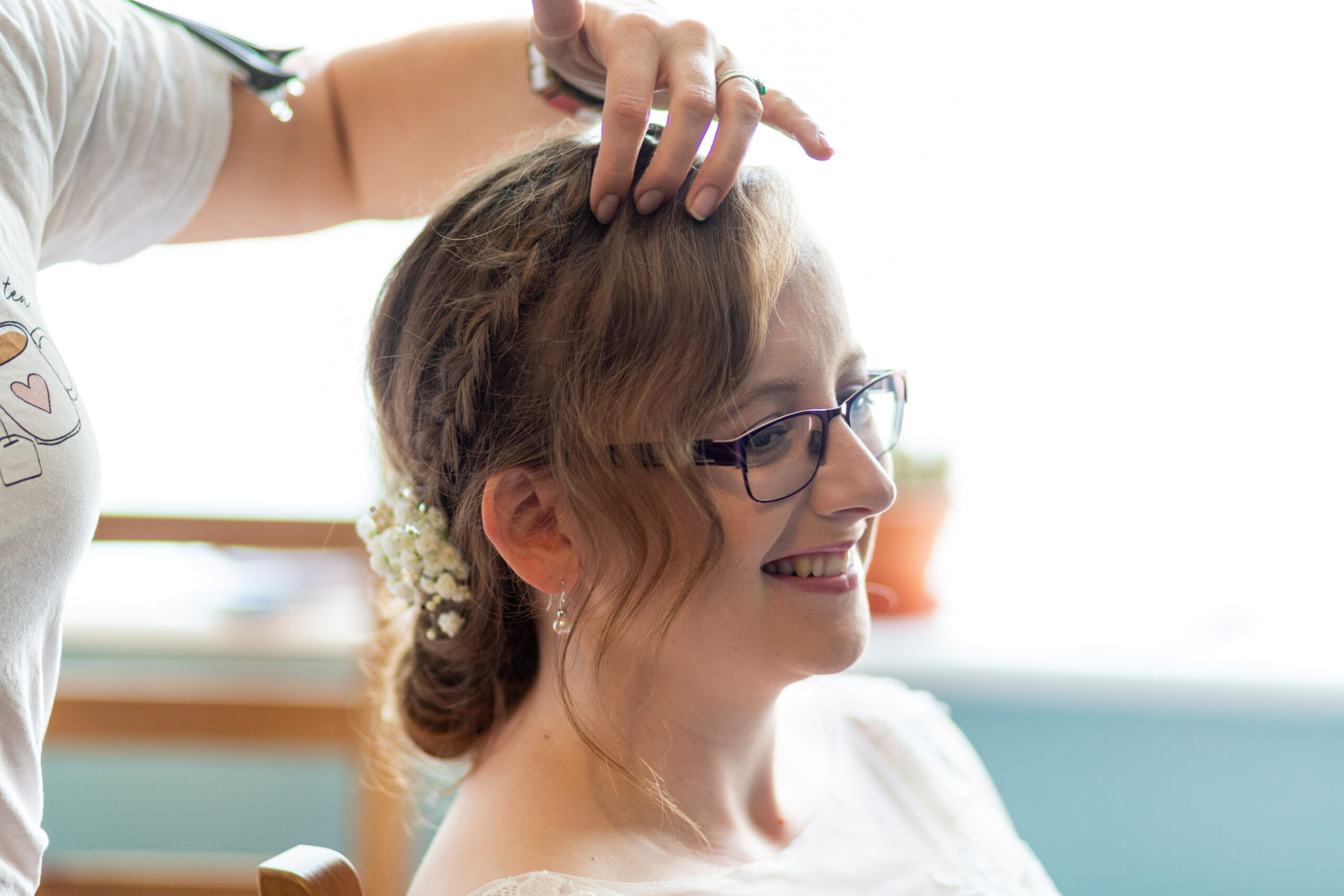 A hand going through the fringe section of a beautiful bridal hair up separating to create texture. A hairstylist doing the finishing touches to a smiling bride wearing glasses. Happy times.