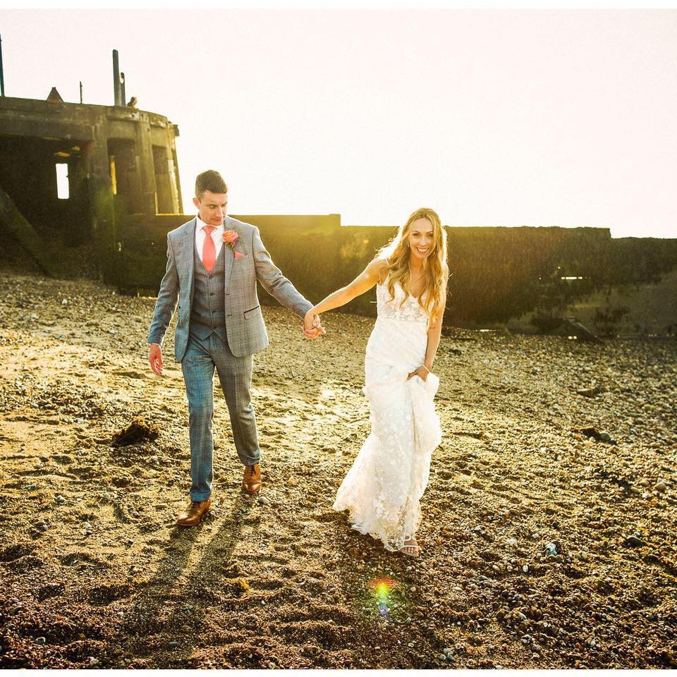 Newly married couple waling along pebble beach, Hand in hand lit with a golden setting sun