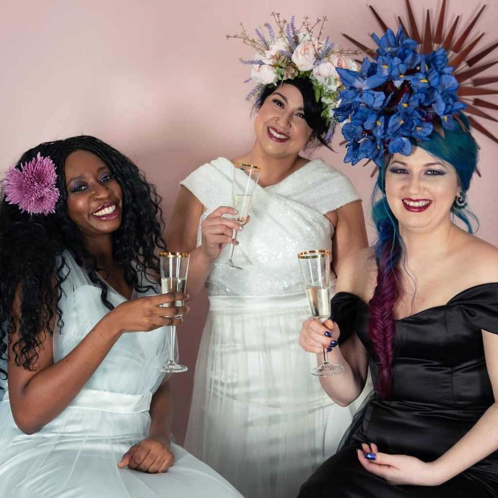 3 beautiful smiling brides celebrating the end of a shoot with champagne. Wearing oversized flower crowns